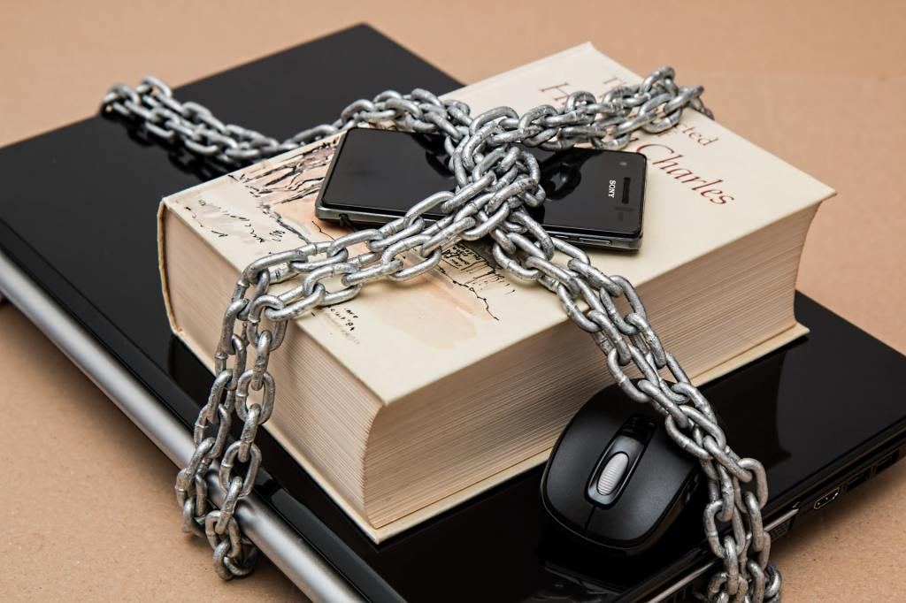A smart phone, a book, and a laptop computer enclosed by thick metal chains